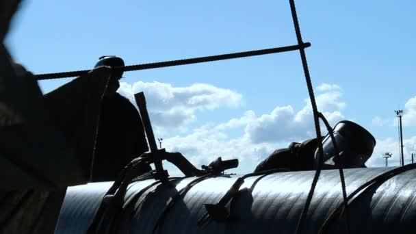men  working at iron pipe
