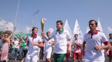Participants running with Olympic fire torch