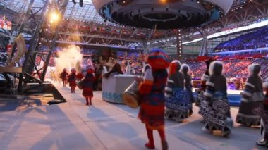 Group of dancers in costumes on modern stadium