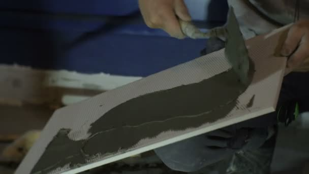 pracovníka uvedení mix lepidla na dlaždice