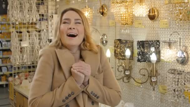 KAZAN/TATARSTAN/RUSSIA - FEBRUARY 04 2016: Beautiful stylish blond woman in beige jacket admired by amazing home lamps collection in modern hardware store on February 04 in KAZAN/TATARSTAN