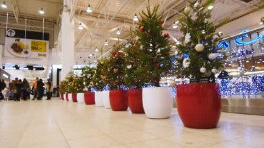 KAZAN, TATARSTAN, RUSSIA - JUNE 12, 2016: Slow motion huge beautiful shopping center decorated with small Christmas trees in pots along luminous fence
