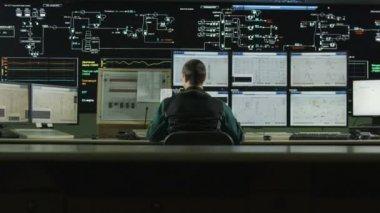 KAZAN, TATARSTAN/RUSSIA - NOVEMBER 15 2016: Backside view camera moves to professional operator answering call at large control panel with screens on November 15 in Kazan