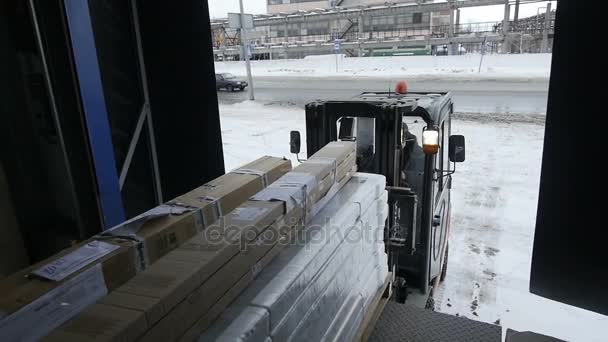 KAZAN, TATARSTAN/RUSSIA - DECEMBER 20 2016: Slow motion worker operates forklift and unloads freight in packaging from lorry against driving cars along road on December 20 in Kazan