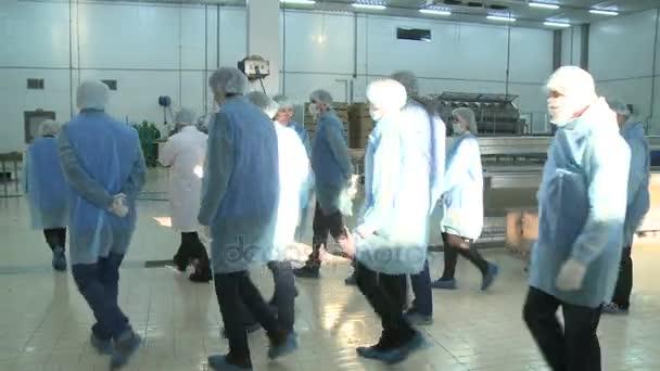 Kazaň, Tatarstán/Rusko - 29 Srpen 2017: Kamera ukazuje skupina studentů ve sterilním kombinézy a masky chůzi o rostlinné skladu pod sluneční světlo na 29. srpna v Kazani