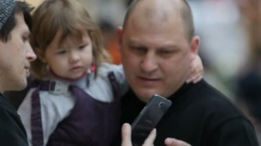 KAZAN, TATARSTAN/RUSSIA - SEPTEMBER 13 2017: Slow motion fat father with little daughter on hands comes to guy takes phone and looks at photo on September 13 in Kazan