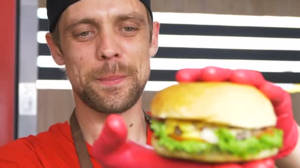 KAZAN, TATARSTAN/RUSSIA - SEPTEMBER 07 2017: Professional joyful chief in red t-shirt shows fresh delicious cheeseburger at food festival on September 07 in Kazan