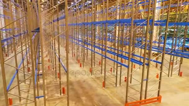 kamera se pohybuje stranou a nahoru podél moderní velké prázdné kovového regálu a pracovník ve stavebnictví ve skladu