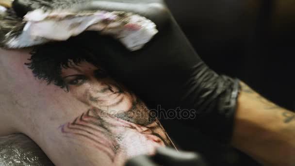 KAZAN TATARSTAN/RUSSIA - NOVEMBER 08 2017: Closeup talented master in black gloves wipes fresh painted tattoo with towel on person body on November 08 in Kazan