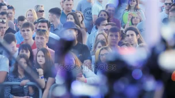 KAZAN TATARSTAN/RUSSIA - NOVEMBER 07 2017: Interested young people behind fence watch celebrity performance on stage at special event in evening on November 07 in Kazan