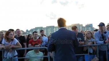 KAZAN, TATARSTAN/RUSSIA - NOVEMBER 07 2017: Camera shows joyful guy showman in stylish costume asking question to music fans at stage against blue sky on November 07 in Kazan