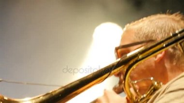 KAZAN, TATARSTAN/RUSSIA - NOVEMBER 07 2017: Closeup side view middle aged man musician in glasses plays horn at performance in evening darkness on November 07 in Kazan