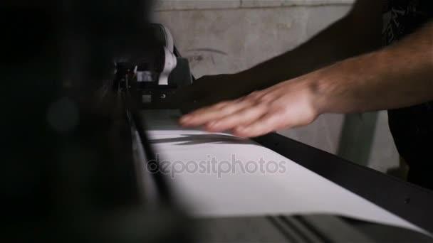 Closeup of male hands preparing paper for digital poster printing machine