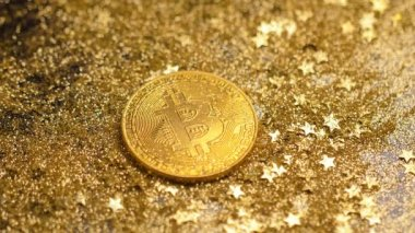 macro amazing shining gold bitcoin model lays among sparkles and stars against bright light