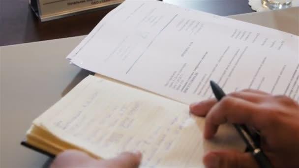 Closeup horní pohled podnikatel otevře notebook s koženým potahem a zapíše nový úkol s perem v tabulka sady office