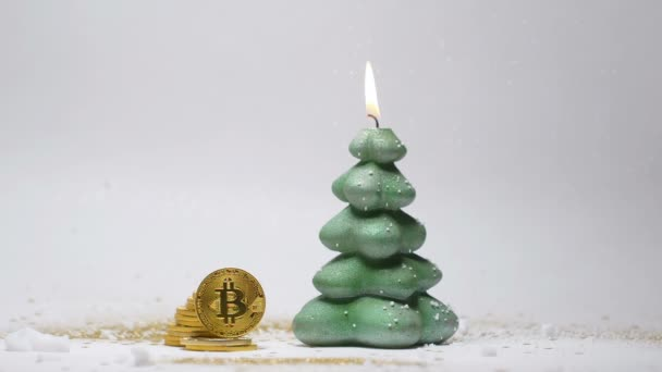 closeup green burning candle in Christmas tree shape and bitcoins with artificial snow against white background