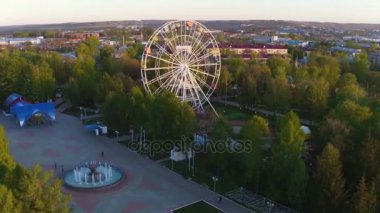 amazing aerial view green fresh park with tracks and large white Ferris wheel among trees against city