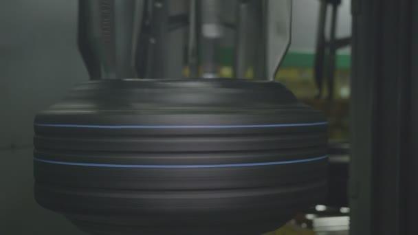 Closeup kruhový mechanismus s velkými háčky rotující Gumové pneumatiky dokončí proces výroby pneumatiky