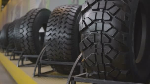 Closeup produced rubber tires with different types of protectors stand on  shelf in showroom