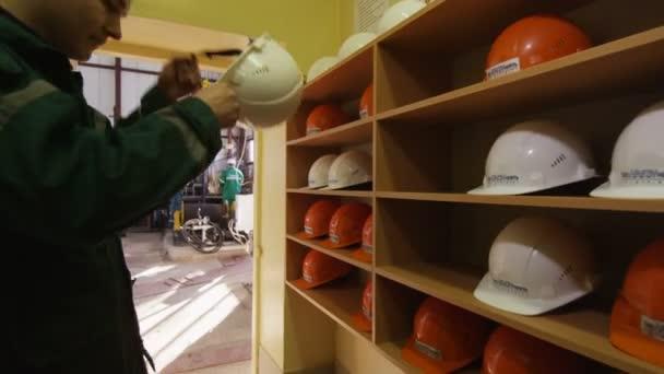 Kazaň, Tatarstán/Rusko - 23 srpna 2017: Bruneta Closeup zaměstnance v zelené uniformě s logem ropné společnosti klade na helmu a jde do zdvihu jeřábu na 23. srpna v Kazani
