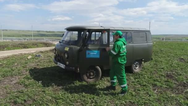 Kazaň, Tatarstán/Rusko - 22 srpna 2017: Detailní řidič v uniformě s logem společnosti ropné vymkne auto a sedí na notebooku zkoumat na ropná pole na 22. srpna v Kazani