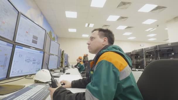 Kasan, Tatarstan/Russland - 19. September 2017: Closeup Gas Unternehmen Arbeiter sitzt am Computer beobachten Produktionsprozess und bespricht mit Kollegen am 19. September in Kasan