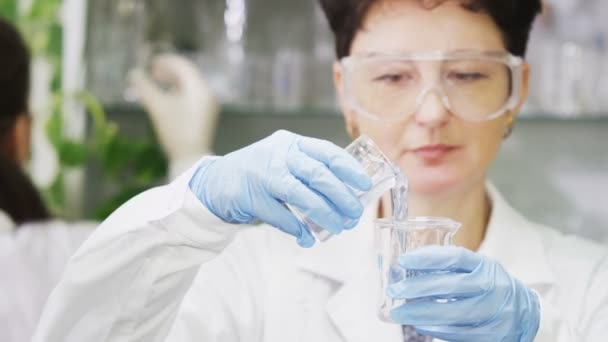kasan, tatarstan / russland - 23. August 2017: Eine gelernte Laborantin im weißen Kittel gießt am 23. August in kasan Schleimflüssigkeit in Laborgläser