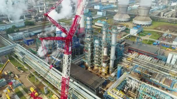 Luftaufnahme großer Metalltanklinien und hoher Türme auf dem Gelände der Ölraffinerie vor dem Himmel mit weißen Wolken