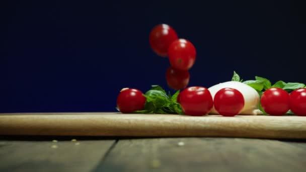 zralá cherry rajčata padají na stůl zpomaleně