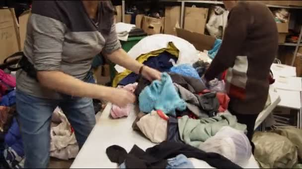 women check second hand clothes on table in storage closeup