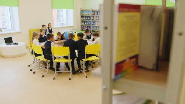 little students work sitting around table with large globe
