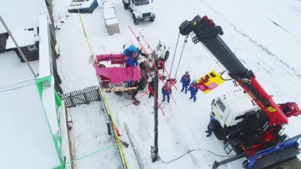 elektrikáři opravit přerušené vedení v zimní vesnici