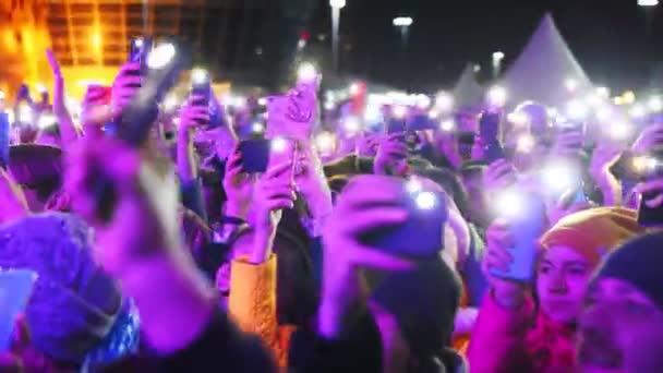 glückliche Menschen mit Taschenlampen genießen Show in der Nähe des neuen Zentrums