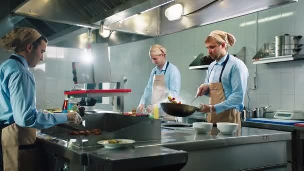 muži připravit jídlo s čerstvými ingrediencemi na velkých kamnech