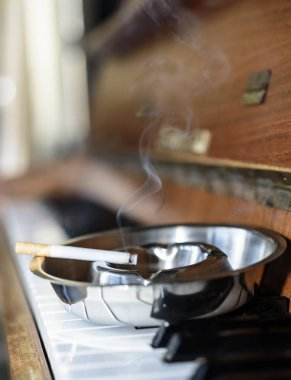 Ashtray on the piano keyboard , cigarette, blurred background