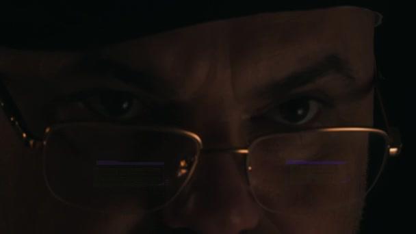 ein Hacker in einem dunklen Raum, der sich im Monitor widerspiegelt