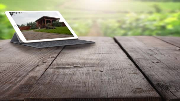 Tablet PC and keyboard on the wooden table outdoors. Looking at home security cameras on tablet computer