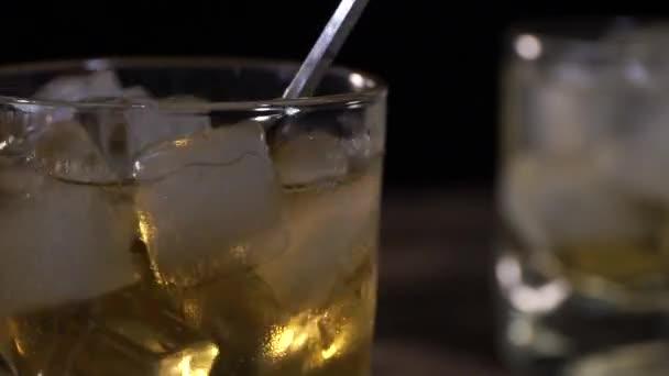 Csapos keverő jégkockák egy pohár bárkanállal a fa pult