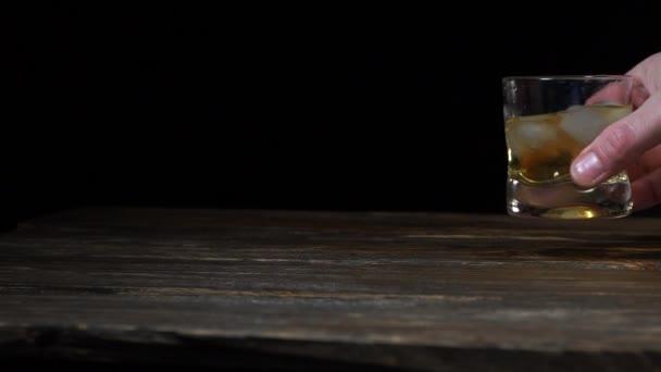 Kézzel fog egy pohár whiskey-t jégkockákkal a fekete háttéren. Ember rázza whiskey üveg jégkockákkal