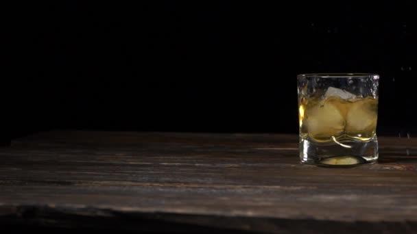 A jégkockák beleesnek egy pohárba arany maláta whiskyvel.