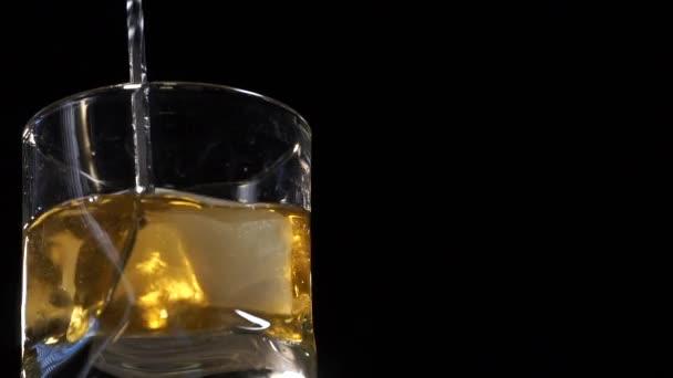 A csapos jégkockákat keverget egy pohárban, bárkanállal a bárpulton. Szelektív fókusz. Lassú mozgás.