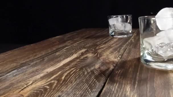 Eiswürfel fallen in ein Glas. Zeitlupe