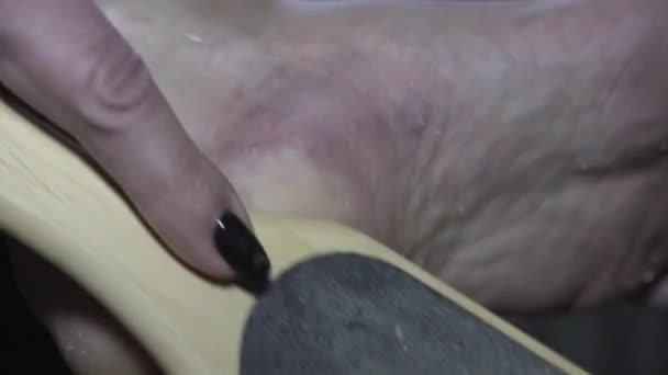 Zavřít. Pedikúru v domě. Starají se o nehty na pedikúře. Peeling feet pedicure procedure