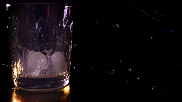 Arany whisky vagy konyak jégkockás pohárba öntése