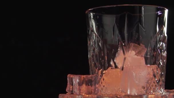 Stará whisky nalévá do skla. Nalití skotské whisky nebo koňaku do sklenic s kostkami ledu na tmavém pozadí