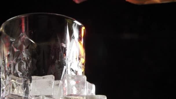 Régi Whiskey öntött az üvegbe. Whiskey vagy konyak öntése sötét alapon jégkockákkal borított poharakba