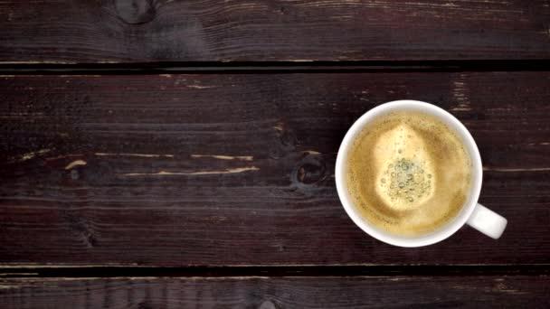 Horký šálek kávy na starém dřevěném stole. Z hrníčku horké kávy stoupá pramínek páry.