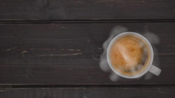 Z hrníčku horké kávy stoupá pramínek páry. Horký šálek kávy na starém dřevěném stolku.Horní pohled. Obchodní a pitné koncepty.