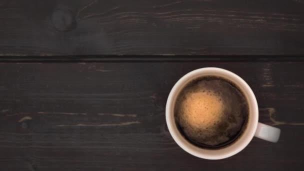 Kávová pěna víří v bílém šálku s kávou. Špinavý tmavě hnědý povrch stolu. Pohled shora dolů. Zpomalený pohyb