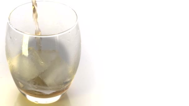 Golden Whiskey Pouring into Glass. Pouring of scotch whiskey or cognac into glasses with ice cubes on white background